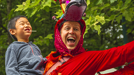 Child laughing with man in red bird costume