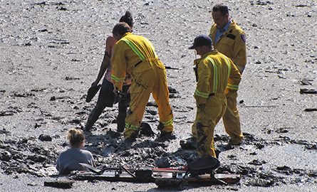 Woman getting rescued from mudflats
