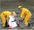 Fire staff rescuing man from mudflats