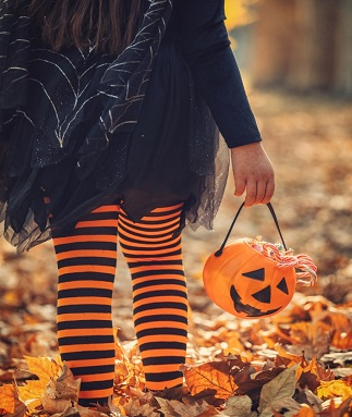 Little girl in witch costume having fun on Halloween