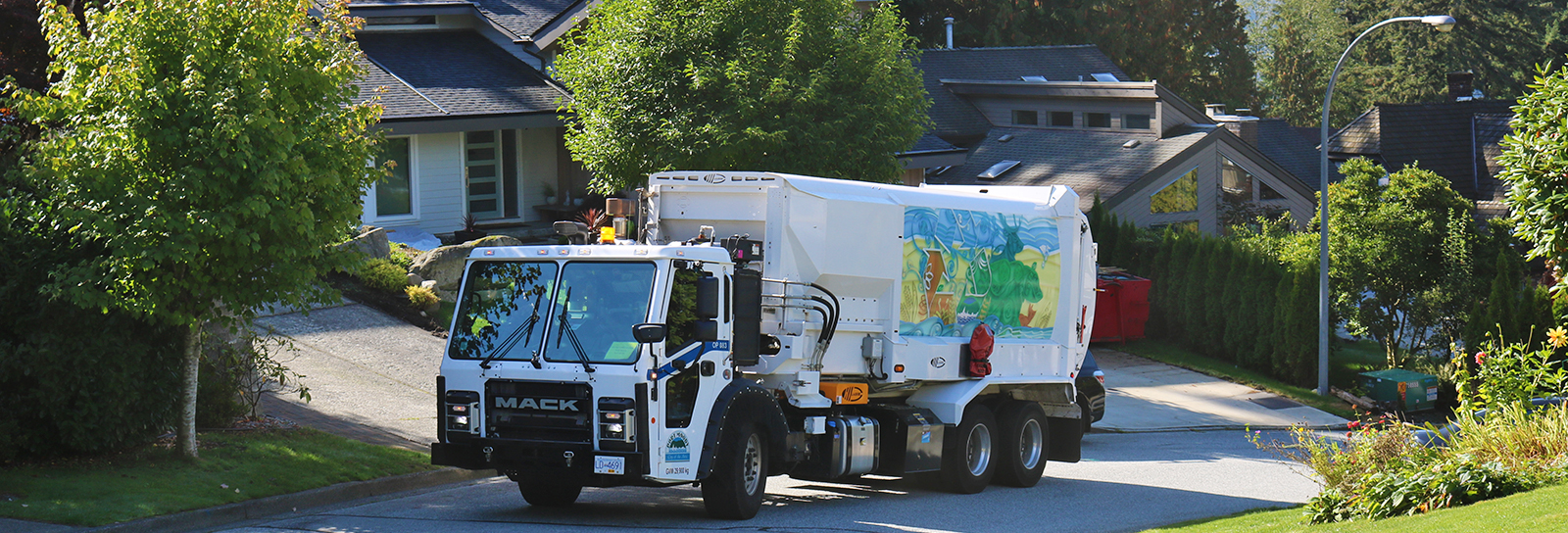 Solid waste collection truck picking up waste in a neighbourhood